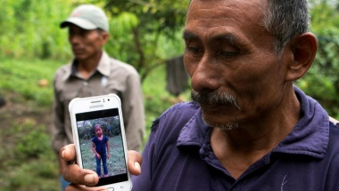 Domingo Caal, 61, grandfather of Jakelin, a 7-year-old girl who died in U.S. custody, holds his mobile phone with a picture of his granddaughter as he stands outside her house in Raxruha, Guatemala December 15, 2018. REUTERS/Josue Decavele