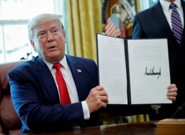 President Donald Trump displays an executive order imposing fresh sanctions on Iran in the Oval Office of the White House in Washington, U.S., June 24, 2019. REUTERS/Carlos Barria