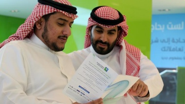 Saudi men check the prospectus of Aramco IPO in Riyadh, November 17, 2019. REUTERS/Ahmed Yosri