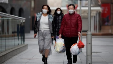 People wearing face masks walk along a street in Beijing, China February 24, 2020. REUTERS/Thomas Peter