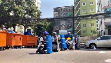 Protesters hide behind barricades during an anti-coup protest in Yangon, Myanmar in this still image from social media video, March 4, 2021. Myanmar Now via REUTERS
