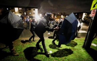 Protesters advance towards officers using umbrellas as shields outside Brooklyn Center Police Department in Minnesota, April 12, 2021. REUTERS/Nick Pfosi