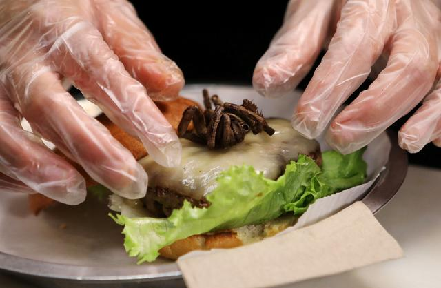 A tarantula burger is prepared at Bull City Burger and Brewery in  celebration of Exotic Meat