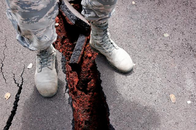 A soldier of the Hawaii National Guard stands over a crack in a road in  Leilani
