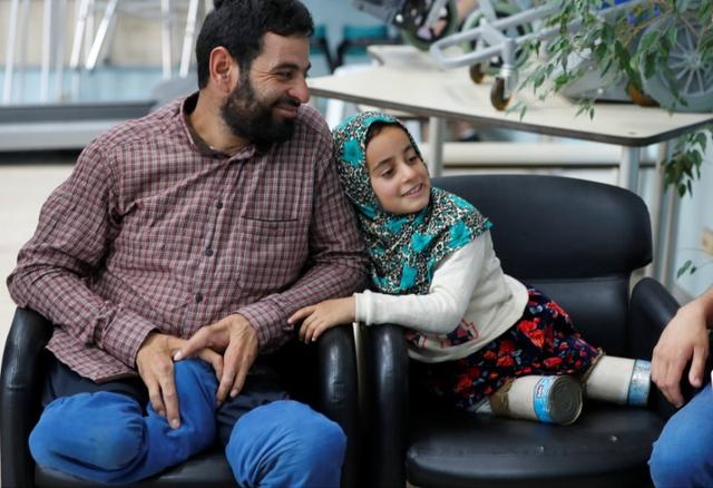 Maya Meri, 8, waits with her father Muhammed Ali Meri at a prosthetic center in Istanbul, Turkey, July 5, 2018. Picture taken July 5, 2018. REUTERS/Osman Orsal