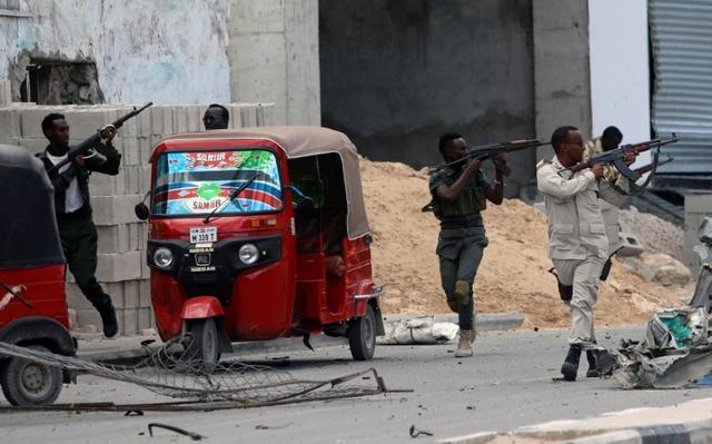 Los agentes de seguridad somalíes toman posición mientras aseguran el lugar de un atentado suicida con coche bomba cerca del palacio presidencial de Somalia en Mogadiscio, Somalia, el 7 de julio de 2018. REUTERS / Feisal Omar
