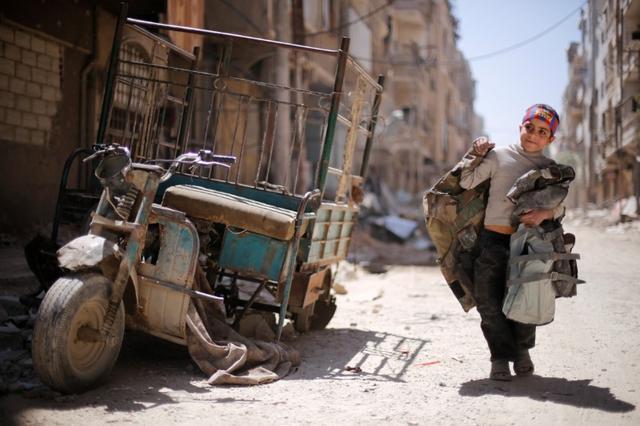 A boy walks along a damaged street at the city of Douma in Damascus, Syria, April 16, 2018. REUTERS/Omar Sanadiki