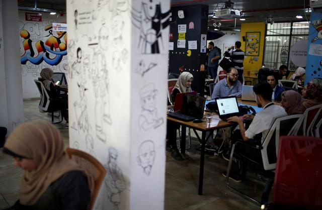 """Miembros del equipo de """"We Are Not Numbers"""" trabajan en computadores portátiles en una oficina en la ciudad de Gaza, el 7 de noviembre de 2018. Fotografía sacada el 7 de noviembre de 2018. REUTERS/Mohammed Salem"""