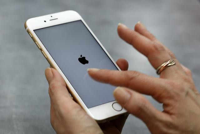 Foto de archivo. Una mujer usa su teléfono móvil, un iPhone 6 de Apple en el centro de Múnich, Alemania. 27 de enero de 2016. REUTERS/Michaela Rehle