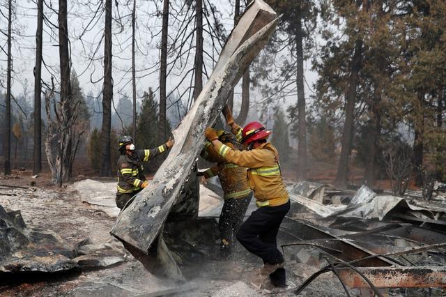 Bomberos mueven escombros mientras recuperan restos humanos de un remolque destruido por el Camp Fire en Paradise, California, EEUU, 17 de noviembre de 2018. REUTERS / Terray Sylvester