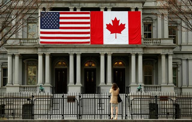 Una mujer se detiene para sacar una fotografía de las banderas de Estados Unidos y Canadá, colocadas una junto a la otra, en el edificio Eisenhower de oficinas para ejecutivos junto a la Casa Blanca, en Washington, el 8 de marzo de 2016. REUTERS/Kevin Lamarque/File Photo
