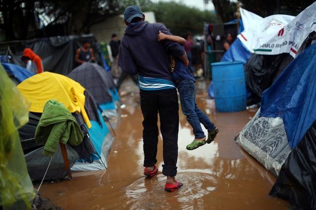 Inmigrantes que forman parte de una caravana de miles de personas de Centroamérica que trata de llegar a Estados Unidos caminan a través de un refugio temporal después de unas fuertes lluvias en Tijuana, México, 29 de noviembre del 2018. REUTERS/Hannah McKay