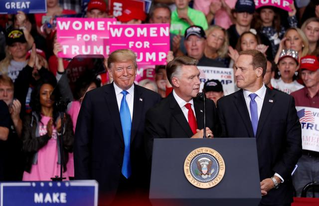 FILE PHOTO: Mark Harris, Republican candidate from North Carolina's 9th Congressional district speaks as U.S. President Donald Trump and Ted Budd, Republican candidate from North Carolina's 13th district look on during a campaign rally in Charlotte, North Carolina, U.S., October 26, 2018. REUTERS/Kevin Lamarque/File Photo