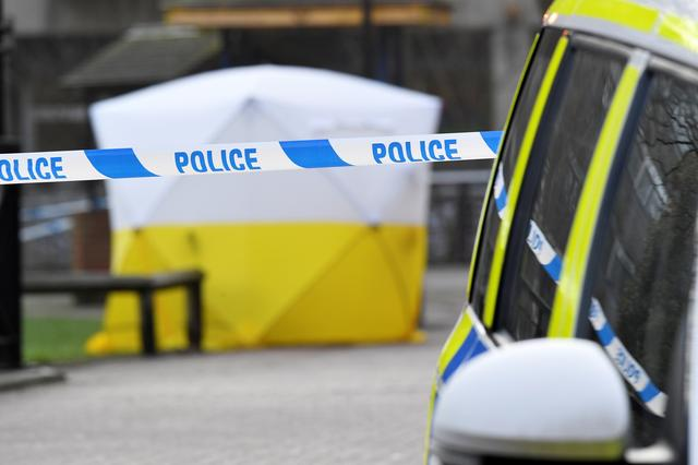 FILE PHOTO: A police car is parked next to crime scene tape, as a tent covers a park bench on which former Russian inteligence officer Sergei Skripal was found unconscious in Salisbury, Britain, March 6, 2018. REUTERS/Toby Melville/File Photo