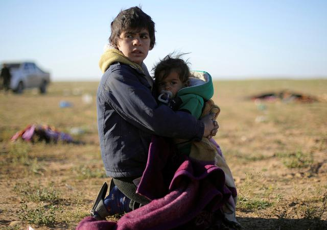 A boy holds a baby near the village of Baghouz, Deir Al Zor province, Syria March 1, 2019. REUTERS/Rodi Said