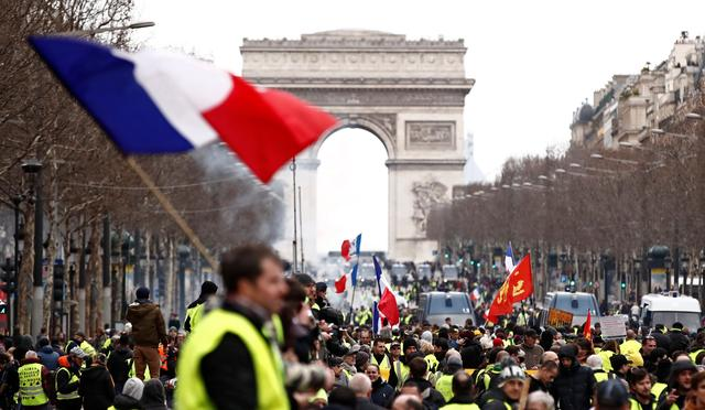 "A protester wearing a yellow vest waves a French flag as he stands on the Champs Elysees near the Arc de Triomphe during a demonstration by the ""yellow vests"" movement in Paris, France, March 2, 2019. REUTERS/Christian Hartmann"