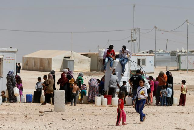 FILE PHOTO: Syrian refugees collect water at the Al-Zaatari refugee camp in Mafraq, Jordan, near the border with Syria August 18, 2016. REUTERS/Muhammad Hamed/File Photo