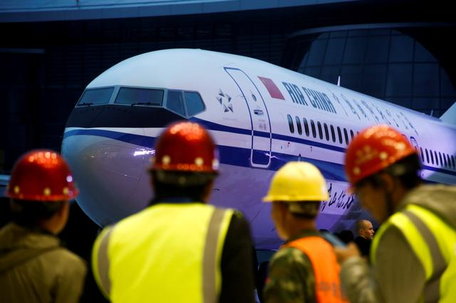 FILE PHOTO: Workers attend a ceremony marking the 1st delivery of a Boeing 737 Max 8 airplane to Air China at the Boeing Zhoushan completion center in Zhoushan, Zhejiang province, China, December 15, 2018.  REUTERS/Thomas Peter/File Photo