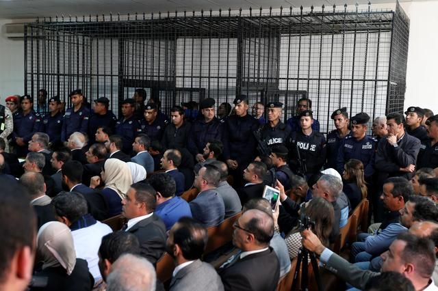 Accused men are seen behind bars during a trial held for over 30 businessmen and customs officials charged with millions of dollars in tax evasion, at the State Security Court, in Amman, Jordan March 12, 2019. REUTERS/Muhammad Hamed