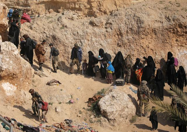 Islamic state fighters and their families walk as they surrendered in the village of Baghouz, Deir Al Zor province, Syria March 12, 2019. REUTERS/Rodi Said
