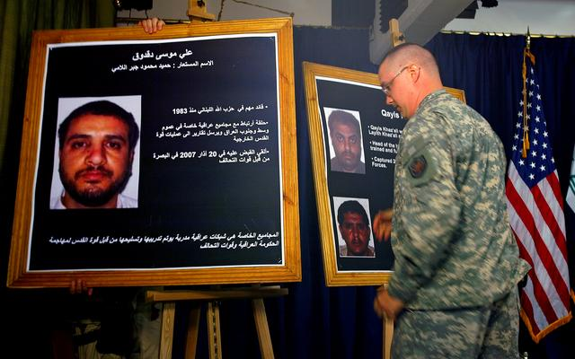 FILE PHOTO: A U.S. solider shows a picture of  Ali Mussa Daqduq (L) during a news conference at the heavily fortified Green Zone area in Baghdad July 2, 2007. REUTERS/Wathiq Khuzaie/Pool (IRAQ)/File Photo