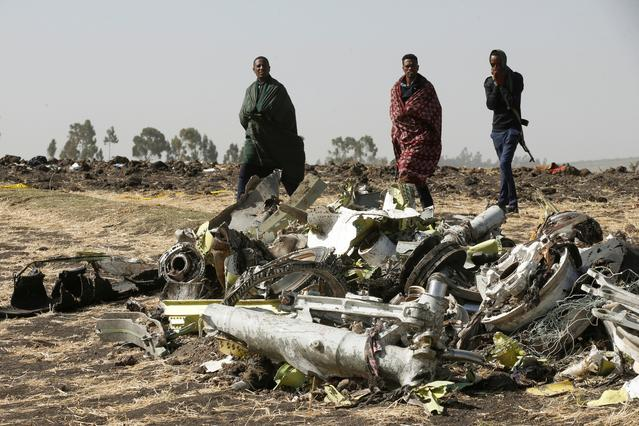 Ethiopian police officers walk past the debris of the Ethiopian Airlines Flight ET 302 plane crash, near the town of Bishoftu, near Addis Ababa, Ethiopia March 12, 2019. REUTERS/Baz Ratner