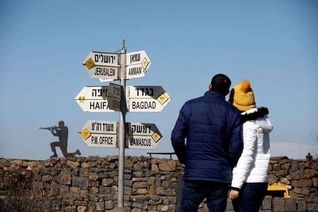 FILE PHOTO: A couple look towards signs pointing out distances to different cities, on Mount Bental, an observation post in the Israeli-occupied Golan Heights that overlooks the Syrian side of the Quneitra crossing, Israel January 21, 2019. REUTERS/Amir Cohen
