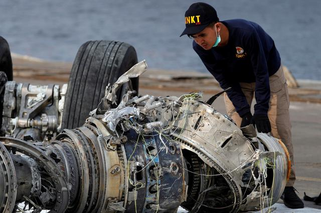 FILE PHOTO: An Indonesian National Transportation Safety Commission (KNKT) official examines a turbine engine from the Lion Air flight JT610 at Tanjung Priok port in Jakarta, Indonesia, November 4, 2018. REUTERS/Beawiharta