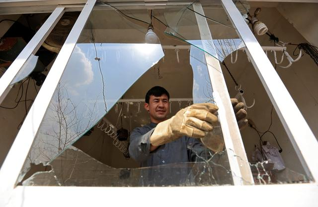 A man removes broken glass from a window after multiple explosions in Kabul, Afghanistan, March 21, 2019. REUTERS/Parwiz