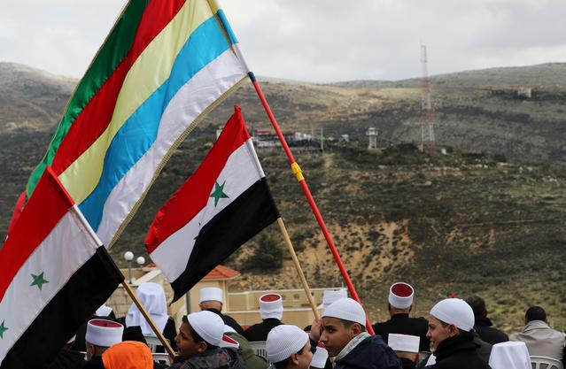 FILE PHOTO: Members of the Druze community holds Syrian and Druze flags as they sit facing Syria, during a rally marking the anniversary of Israel's annexation of the Golan Heights in the Druze village of Majdal Shams, in the Israeli-occupied Golan Heights February 14, 2019. REUTERS/Ammar Awad