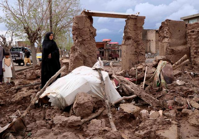 A woman stands next to her house destroyed by flood in Enjil district of Herat province, Afghanistan March 29, 2019. REUTERS/Jalil Ahmad