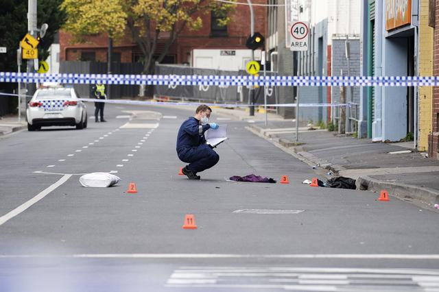 A Victoria Police personnel works at the scene of a multiple shooting outside Love Machine nightclub in Prahran, Melbourne, Australia April 14, 2019. AAP Image/Ellen Smith/via REUTERS