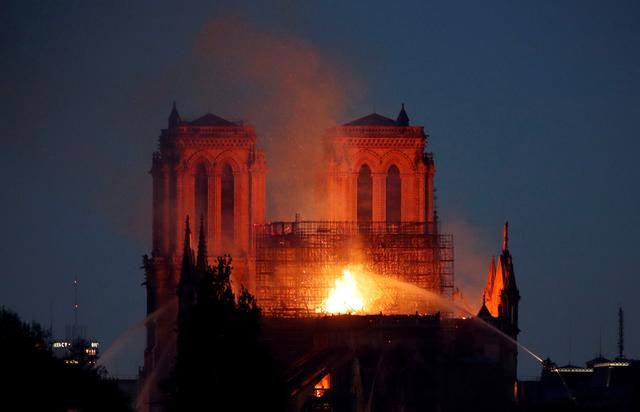 Fire fighters douse flames of the burning Notre Dame Cathedral in Paris, France April 15, 2019. REUTERS/Charles Platiau
