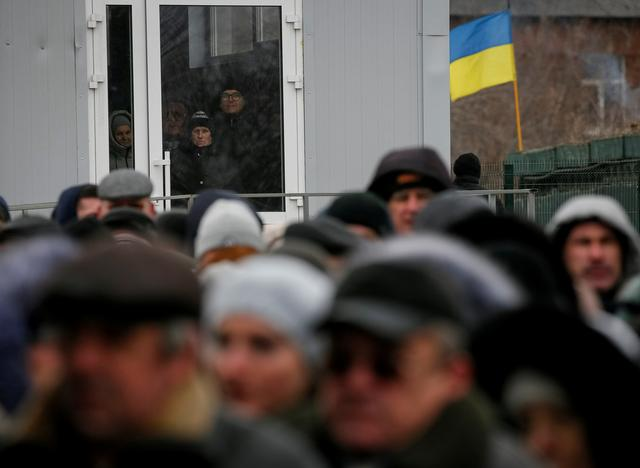 FILE PHOTO: People line up after crossing the contact line between pro-Moscow rebels and Ukrainian troops as they wait at passport control in Mayorsk, Ukraine February 25, 2019. REUTERS/Gleb Garanich/File Photo