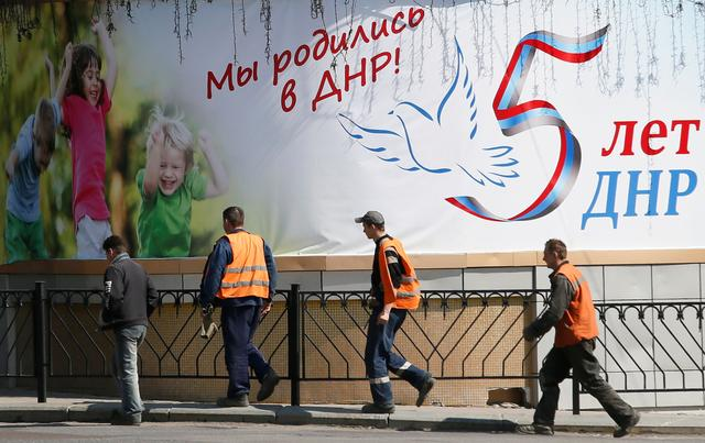 Men walk past a banner, which reads We were born in DPR (Donetsk People's Republic)! DPR is five years old, in a street in the separatist-controlled city of Donetsk, Ukraine April 25, 2019. REUTERS/Alexander Ermochenko