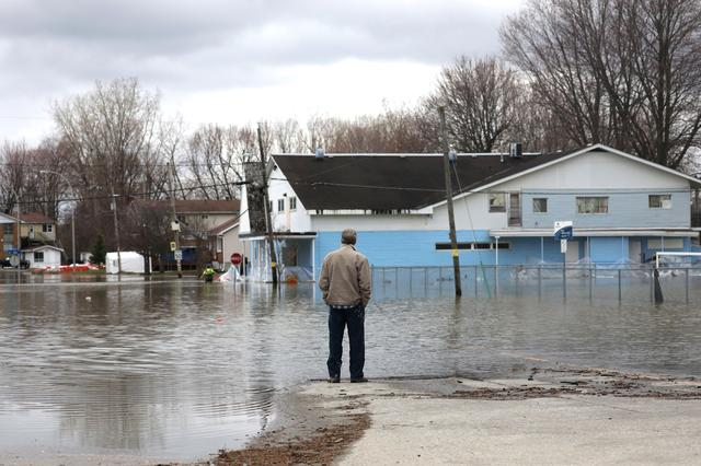 A man looks out at a flooded residential area in Gatineau, Quebec, Canada, April 24, 2019. REUTERS/Chris Wattie