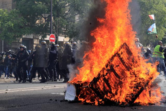 French CRS riot police stand guard next to a fire during clashes as part of the traditional May Day labour union march with French unions and yellow vests protesters in Paris, France, May 1, 2019.  REUTERS/Gonzalo Fuentes