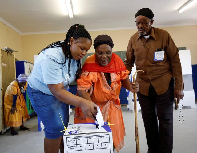 An Electoral Commission of South Africa (IEC) offical assits a blind voter to cast her ballot at a polling station, during the South Africa's parliamentary and provincial elections, in Nkandla, South Africa, May 8, 2019. REUTERS/Rogan Ward