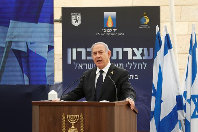 FILE PHOTO: Israeli Prime Minister Benjamin Netanyahu speaks during a ceremony marking Memorial Day, which commemorates the fallen soldiers of Israel, at a monument in Jerusalem, May 7, 2019. REUTERS/Ronen Zvulun