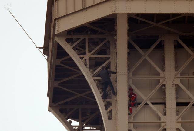 An unidentified man (L) climbs the Eiffel Tower, which had to be evacuated, in Paris, France, May 20, 2019. REUTERS/Charles Platiau