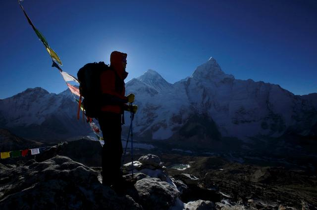 FILE PHOTO: A trekker stands in front of Mount Everest, which is 8,850 meters high (C), at Kala Patthar in Solukhumbu District May 7, 2014. REUTERS/Navesh Chitrakar/File Photo