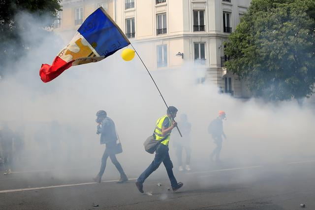 FILE PHOTO: A protester wearing a yellow vest holds a French flag as he walks among tear gas during the traditional May Day labour union march with French unions and yellow vests protesters in Paris, France, May 1, 2019.  REUTERS/Gonzalo Fuentes/File Photo