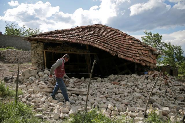 A man walks outside a damaged building after an earthquake stroked the area in Floq, Albania, June 1, 2019. REUTERS/Florion Goga