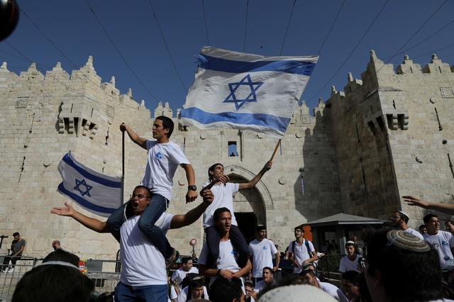 Jewish youth wave Israeli flags as they participate in a march marking Jerusalem Day, near Damascus Gate in Jerusalem's Old City June 2, 2019. REUTERS/Ammar Awad