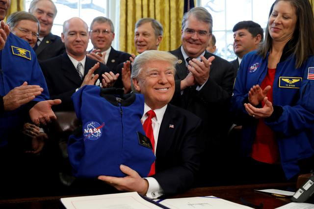 FILE PHOTO: U.S. President Donald Trump receives a NASA jacket during a signing ceremony for S442, the NASA transition authorization act, in the Oval Office of the White House in Washington, U.S., March 21, 2017.   REUTERS/Kevin Lamarque/File Photo