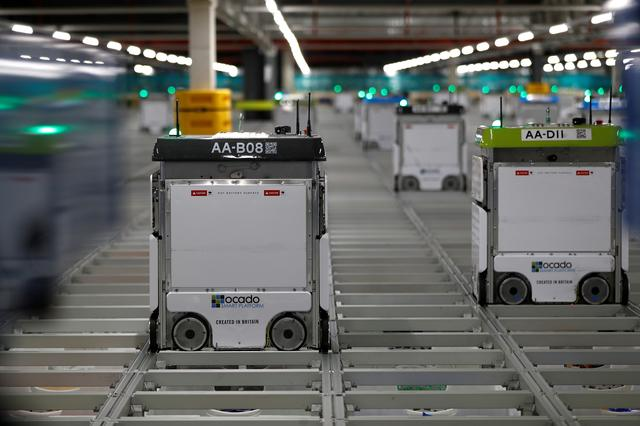 "FILE PHOTO: ""Bots"" are seen on the grid of the ""smart platform"" at the Ocado CFC (Customer Fulfilment Centre) in Andover, Britain May 1, 2018. Picture taken May 1, 2018.  REUTERS/Peter Nicholls/File Photo"