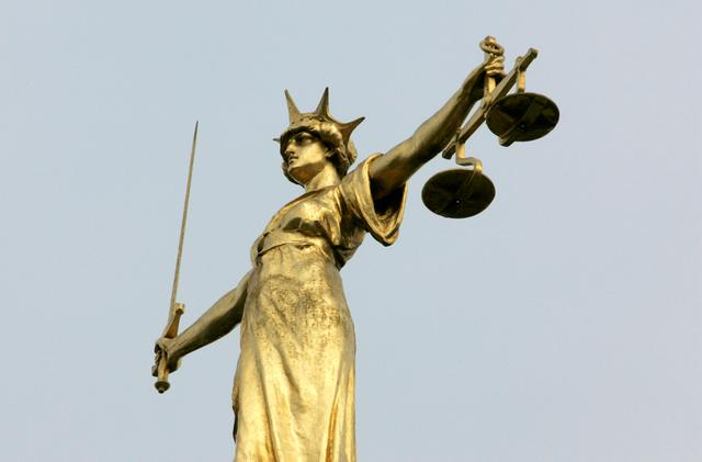 FILE PHOTO: A statue representing the scales of justice is seen on the roof of the Old Bailey courts in central London, January 26, 2007. REUTERS/Toby Melville/File Photo