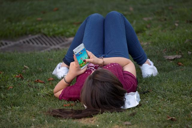 FILE PHOTO: A woman plays a game on her cell phone while lying on the grass in Madrid, Spain, July 4, 2017. REUTERS/Juan Medina