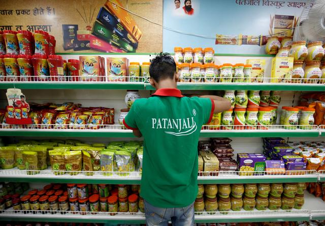 FILE PHOTO: A worker arranges consumable goods inside a Patanjali store in Ahmedabad, India, March 28, 2019. REUTERS/Amit Dave