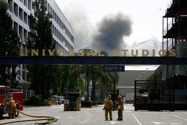 FILE PHOTO: A fire truck and firefighters are seen at Gate 2 of Universal Studios as smoke rises (background) from a fire that rages out of control at the backlot filled with movie sets in Universal City, California June 1, 2008.    REUTERS/Fred Prouser/File Photo
